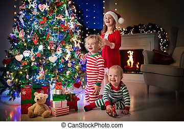 Children at Christmas tree. Kids at fireplace on Xmas eve -...