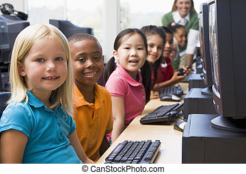 Children at computer terminals with teacher in background...