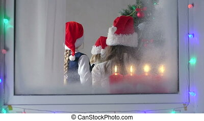 Children at home decorating Christmas tree view through the window