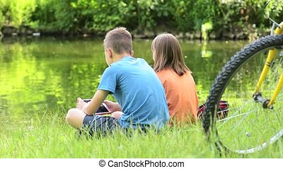 Children at lakeside - Children - girl and boy, with tablet...