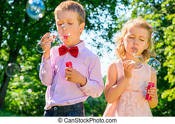 children at the celebration with soap bubbles on a summer day