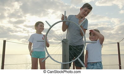 Children at the helm of the ship. Happy childhood