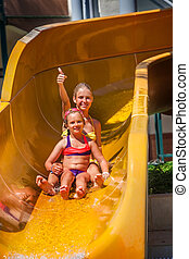 Children at water park slide down and show thumbs up.