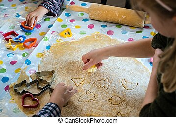 Children Baking Christmas Cookies cutting pastry with a cookie cutter