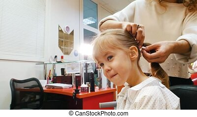 Children barbershop. Hairdresser with little blonde girl....