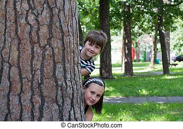 children behind a tree