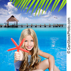 children blond girl in summer vacation tropical beach with starfish