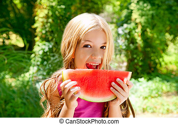 Children blond little girl eating watermelon slice in forest