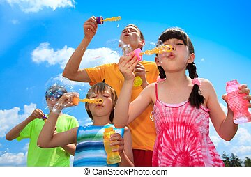Children having fun, blowing bubbles on a sunny day.
