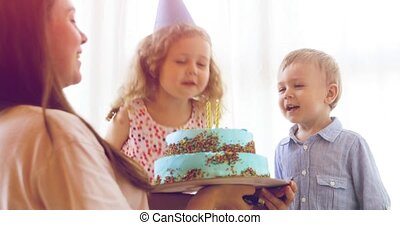 Children blowing candles on cake