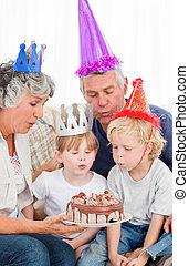 Children blowing on the birthday cake