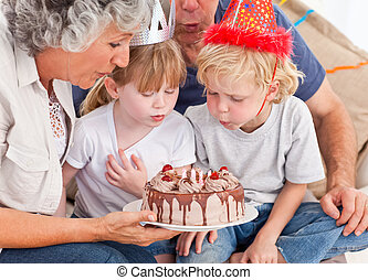 Children blowing on the cake