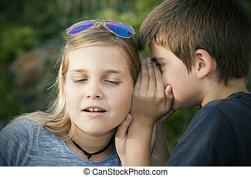 children - boy and girl counting a secret to the ear....