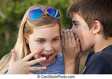 children - boy and girl counting a secret to the ear