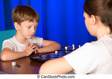 Children boy and girl playing a board game