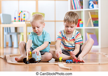 Children boys playing rail road toy in nursery