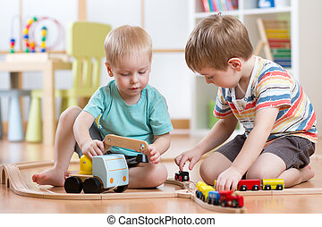 Children boys playing railroad together in playroom