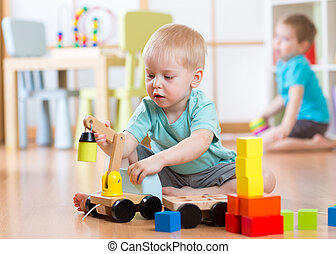 Children boys playing with toy crane in playroom