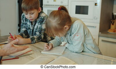 Children brother and sister are doing homework with dad then enjoying successful results and doing high-five at home in kitchen. Fatherhood and education concept.