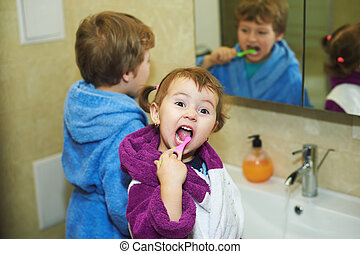 Children brush their teeth morning in the bathroom , dressed in robes