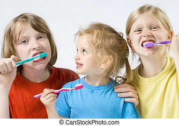 Children brushing teeth - Little girl wearing colorful t-...
