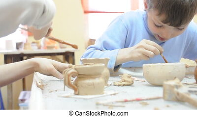 children brushing their pottery