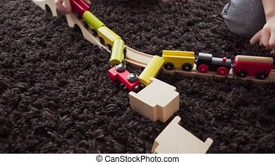 Children build wood model toy locomotive on the floor in a...