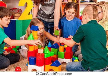 Children building blocks in kindergarten. Group kids playing toy floor .