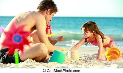 Children building sand castles with their father