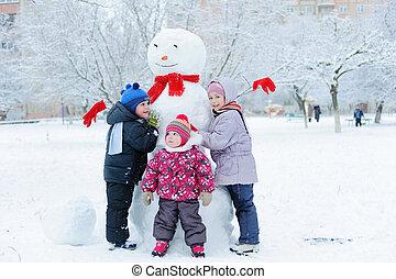 Children building snowman in garden