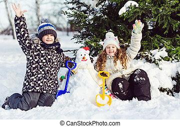 Children building snowman in the park.