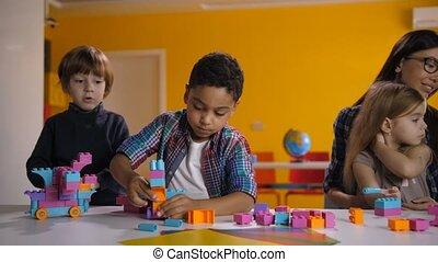 Children building with bright constructing bricks - Joyful...