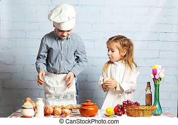 Children chefs. little brother and sister cook in the kitchen. Little boy preparing dough for bread.