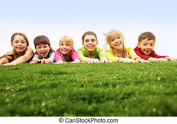 CHildren having rest on lawn