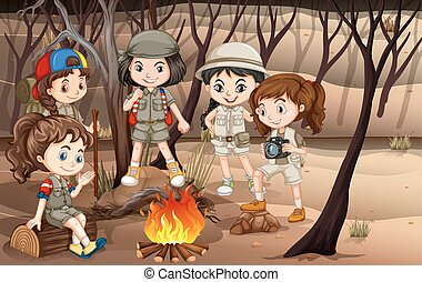 Children circle around the campfire in the woods