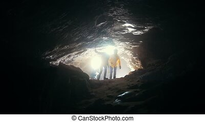Children come into the cave - Two girls and a boy go into...