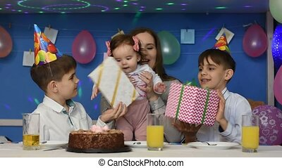 Children congratulate the one-year-old girl with a happy birthday and give gifts