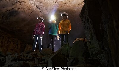 Children consider the room in the cave - Two girls and a boy...