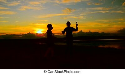 Children dance in the beautiful fiery sunset