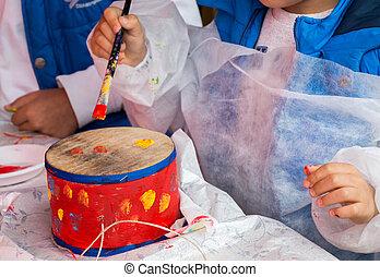Children decorating handmade drum