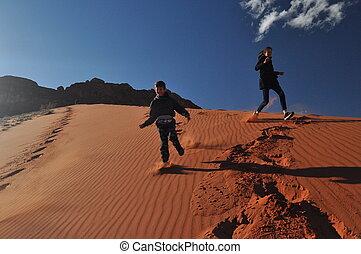 Children descending from a high, sandy dune in the Wadi Ram desert in Jordan. Great fun when traveling to a distant country.
