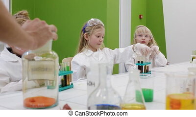 children do an experiment in a chemistry lesson. modern...