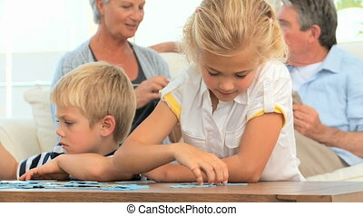 Children doing a puzzle while their grand parents are  talking