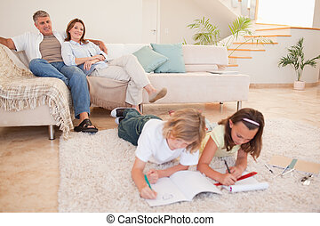 Children doing homework with parents behind them