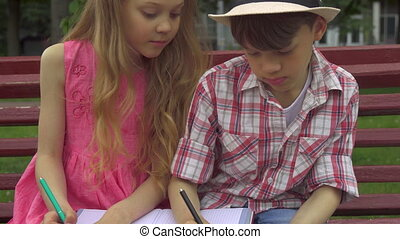 Children draw in the album together on the bench
