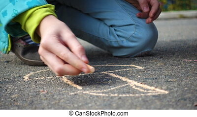 children drawing on an asphalt with the piece of chalk