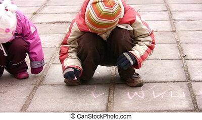 children drawing on asphalt panning - Children drawing on...