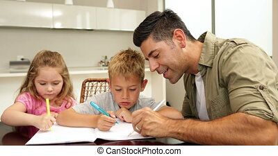 Children drawing with their dad at the table at home in...