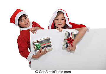 children dressed in Christmas costume with gifts