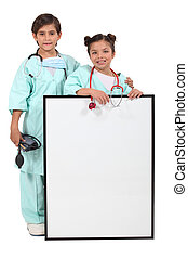 Children dressed up as doctors and standing behind a blank sign